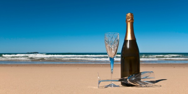 Bottle of champagne with two crystals glasses on a secluded beach.