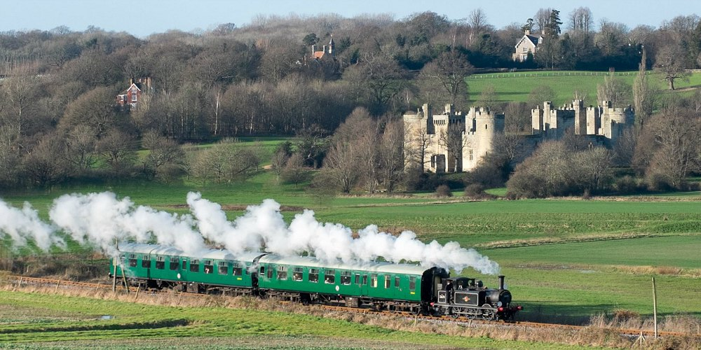steam train passing bodiam castle